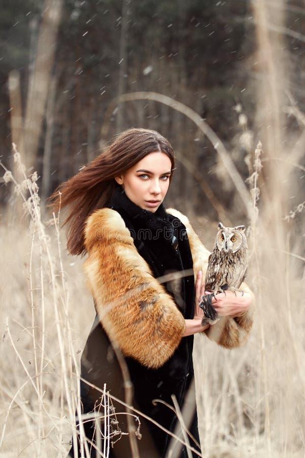 Femme en automne dans le manteau de fourrure avec la première neige de hibou en main Belle fille de brune avec de longs cheveux e photo libre de droits