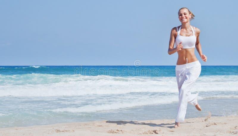 Femme en bonne santé courant sur la plage images libres de droits