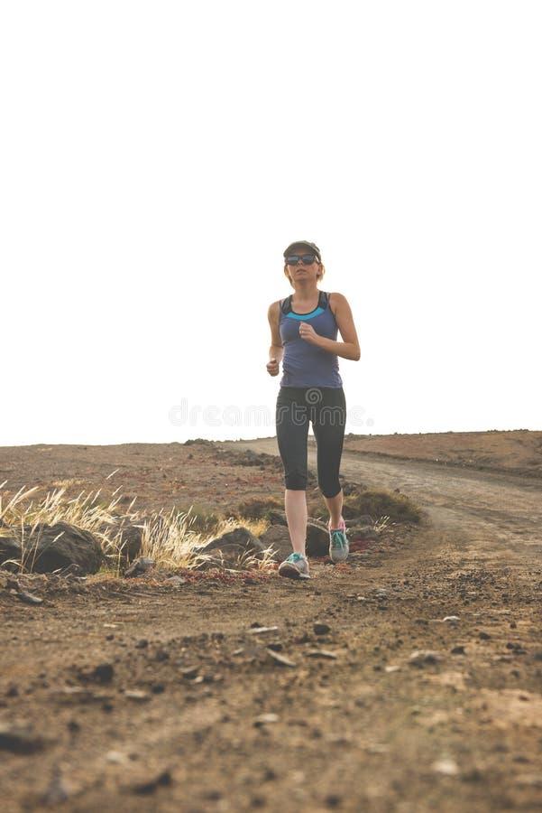 Femme en bonne santé courant sur le chemin de terre photographie stock