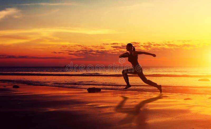 Femme en bonne santé de forme physique courant au coucher du soleil images libres de droits