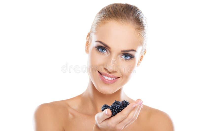 Femme en bonne santé de sourire avec des mûres image stock