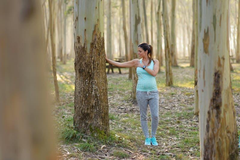 Femme en bonne santé enceinte sur la séance d'entraînement extérieure de forme physique étirant le che images stock