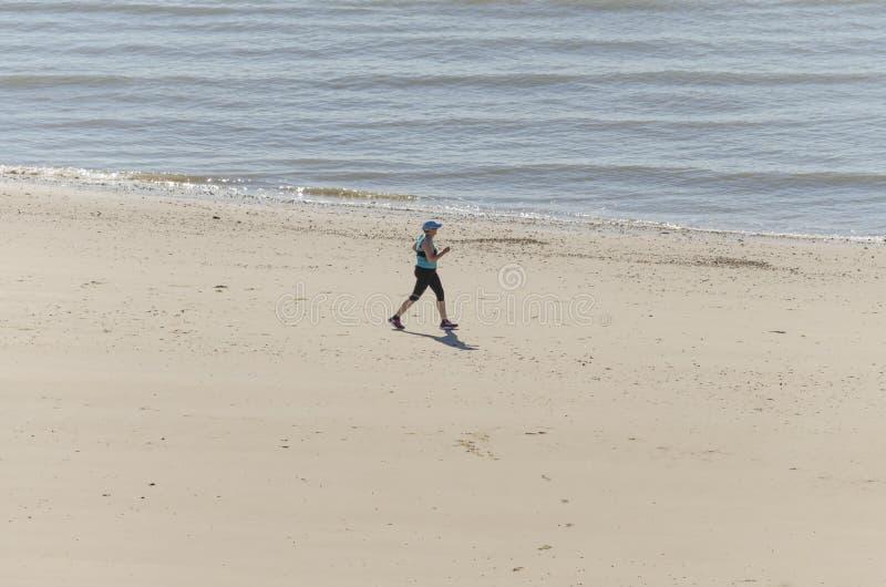 Femme en bonne santé exécutant sur la plage photographie stock libre de droits