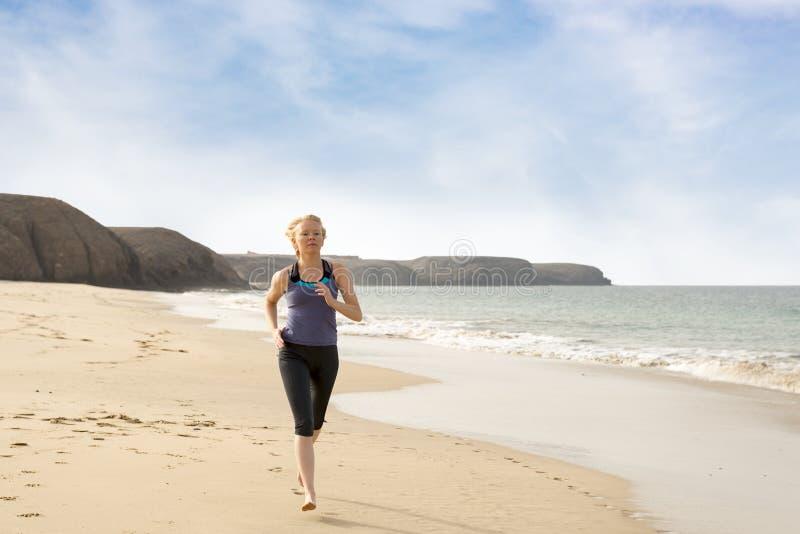 Femme en bonne santé pulsant le long de la plage images libres de droits
