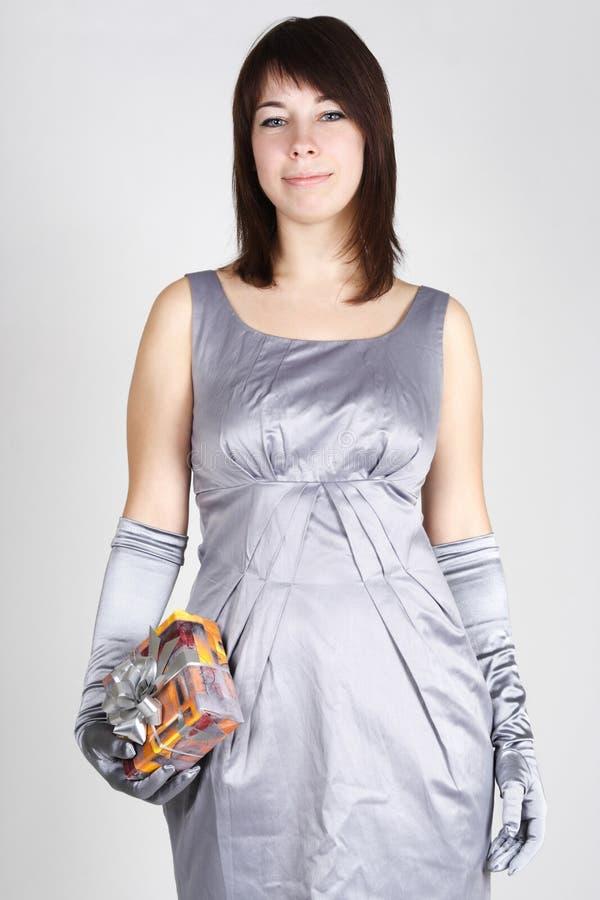 Femme en cadeau argenté de fixation de robe de soirée photographie stock libre de droits