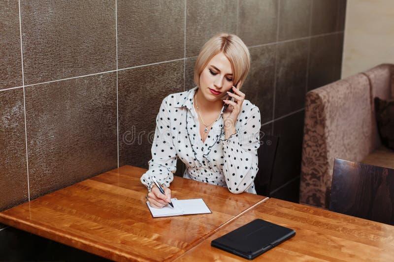 Femme en café parlant au téléphone et écrivant dans le carnet photo libre de droits