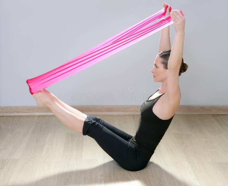 Femme en caoutchouc rouge de gymnastique de bande de résistance de yoga de Pilates photo libre de droits