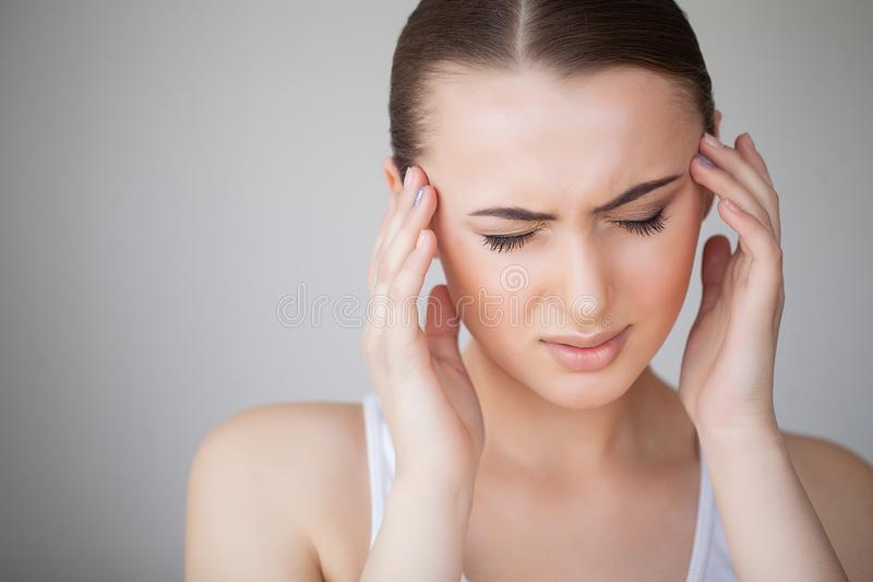 Femme en douleur se sentant mauvaise et en difficulté, ayant le mal de tête et la fièvre, tenant la main sur le front Belle fille photo stock
