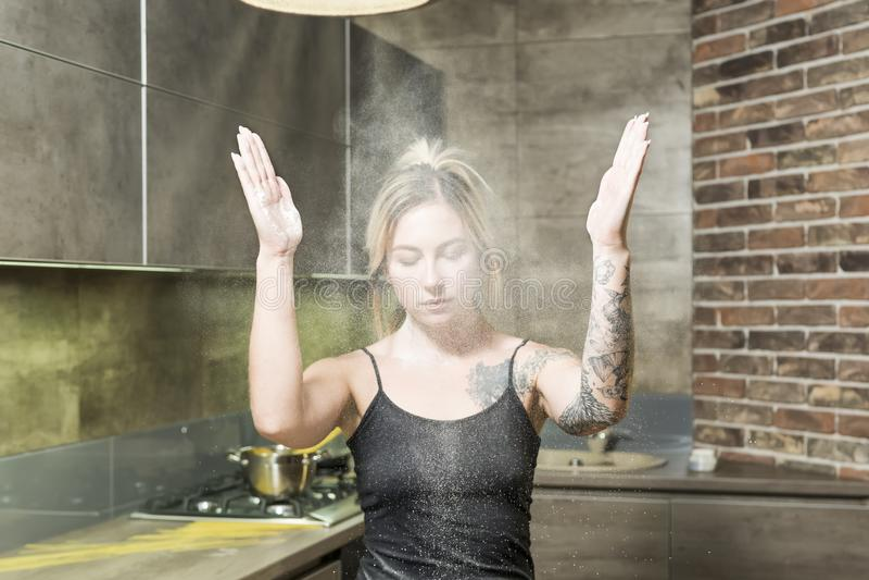 Femme en farine sur la cuisine photo stock