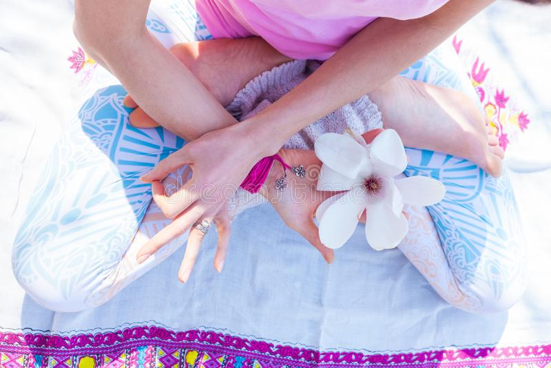 Femme en fleur symbolique de prise de posture de lotus de yoga dans une main et toute autre main dans le geste de mudra du jour d photos stock