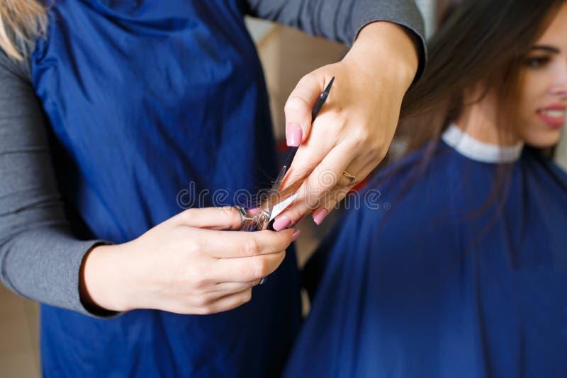 Femme en gros plan de coiffeur dénommant de longs cheveux sur un fond de boutique Coiffeur au travail Concept de soins capillaire photographie stock