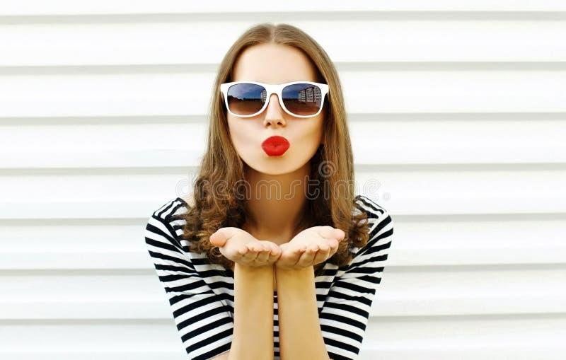 Femme en gros plan de portrait soufflant les lèvres rouges envoyant le baiser doux d'air sur le mur blanc images libres de droits