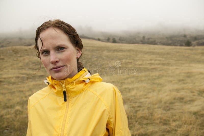 Femme en jaune sur la descente de jour pluvieuse photos libres de droits