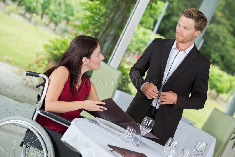 Femme en nourriture de commande de fauteuil roulant image stock