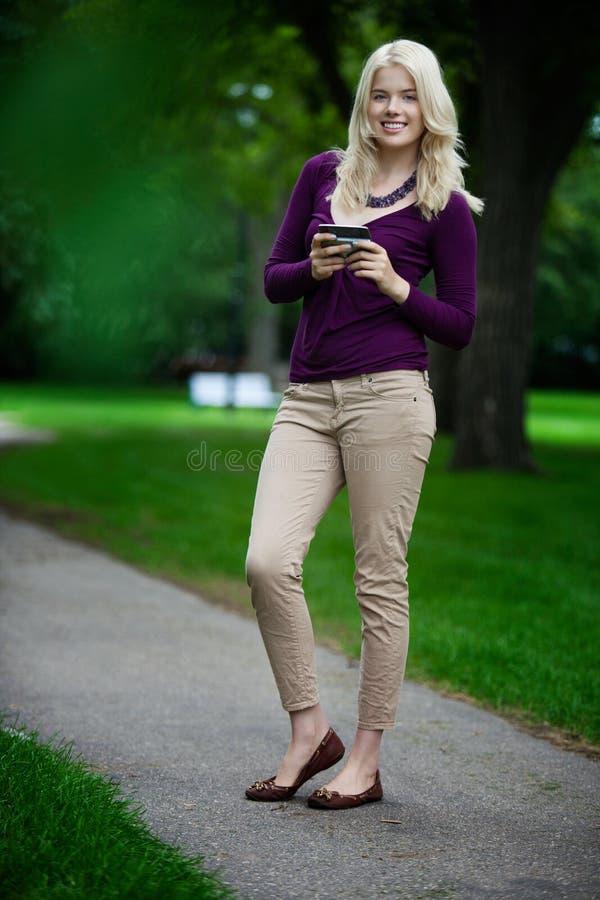 Femme en parc avec le téléphone portable photographie stock libre de droits