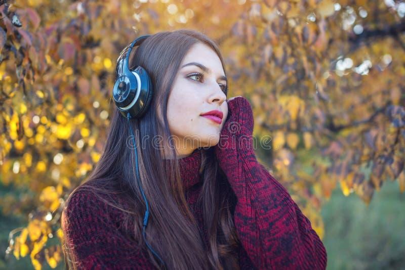 Femme en parc d'automne se tenant écoutant la musique avec ses écouteurs Concept de bonne humeur, musique préférée, temps heureux images libres de droits