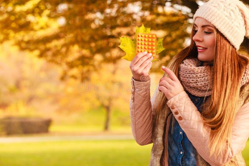 Femme en parc d'automne tenant des médecines de vitamines photo libre de droits