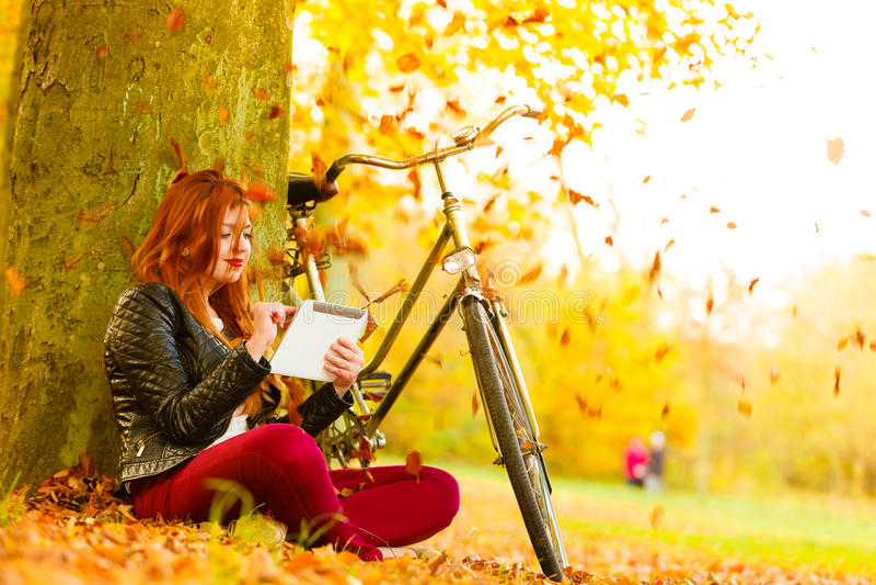 Femme en parc d'automne utilisant la lecture de tablette image libre de droits