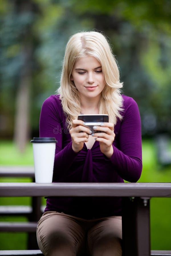 Femme en parc utilisant le téléphone portable photo libre de droits