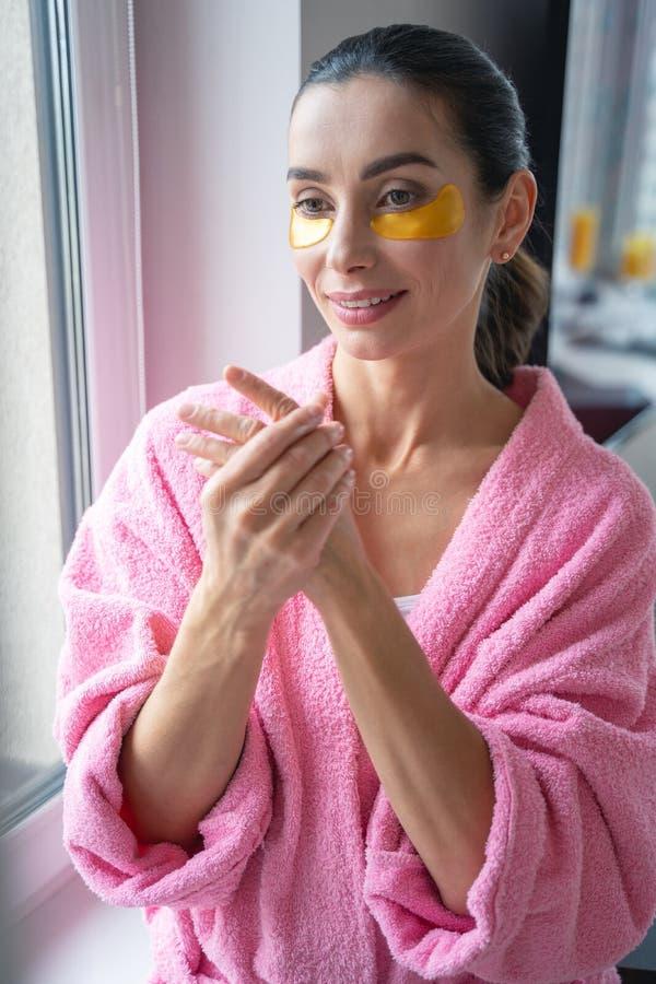 Femme en peignoir appliquant une photo de bouillon de lotion photo libre de droits