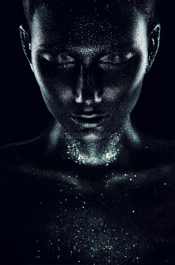 Femme en peinture noire avec des étincelles dans l'obscurité
