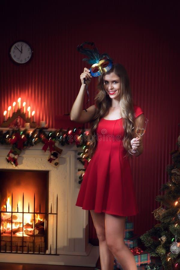 Femme en robe rouge avec champagne dans l'environnement de Noël photos stock