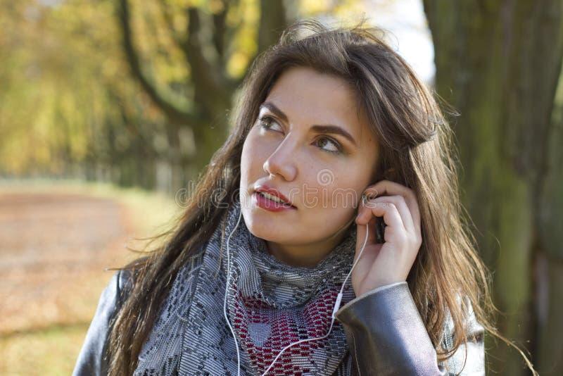 Femme en stationnement avec des écouteurs images stock