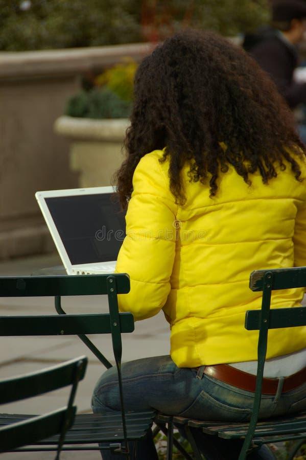 Femme en stationnement utilisant l'ordinateur portable photo stock
