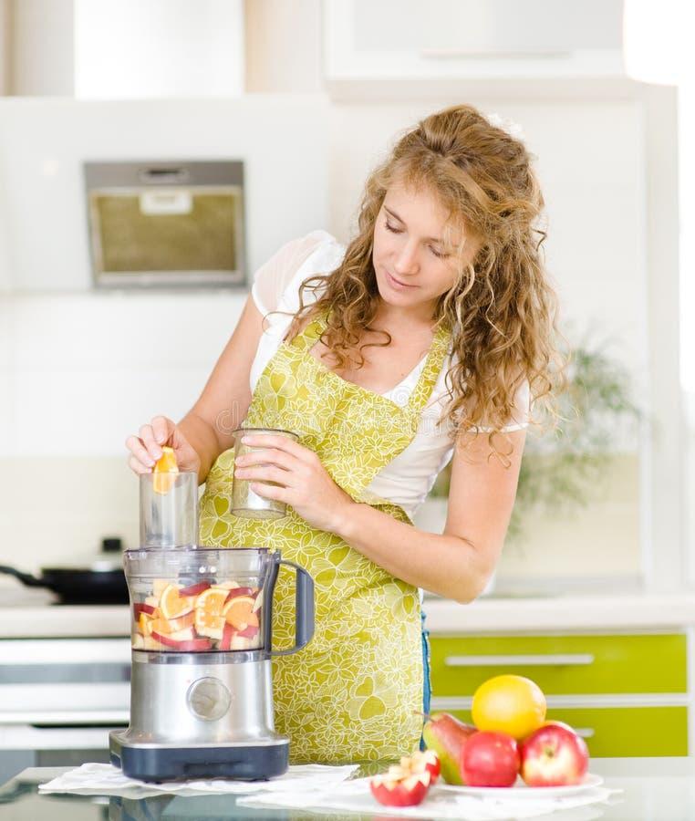 Femme enceinte à l'aide d'un presse-fruits images stock