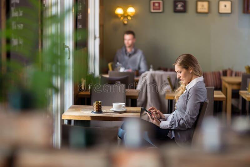 Femme enceinte à l'aide de la Tablette de Digital au café photo libre de droits