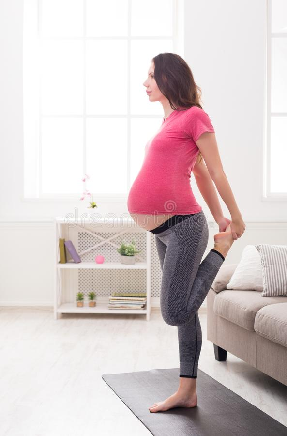 Femme enceinte étirant des jambes s'exerçant à l'intérieur images stock