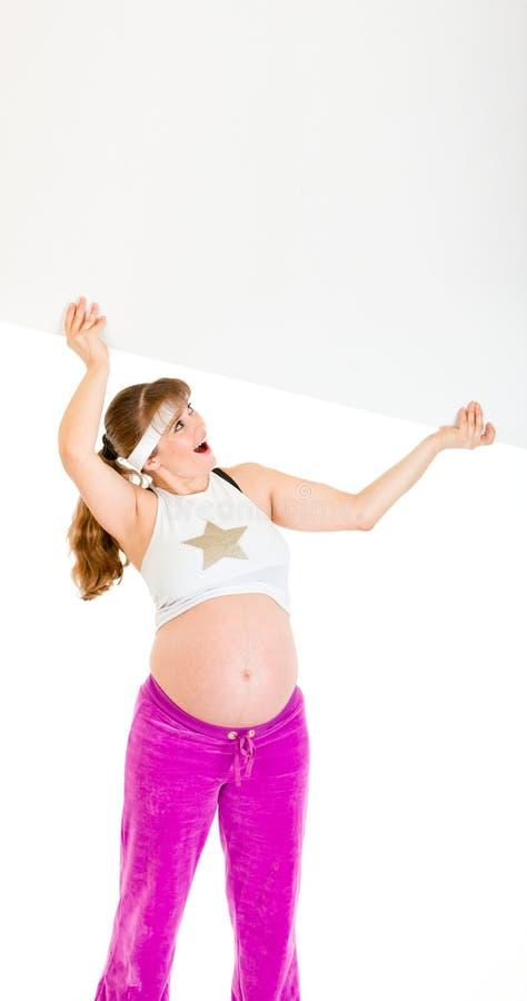 Femme enceinte étonné retenant le panneau-réclame blanc image libre de droits