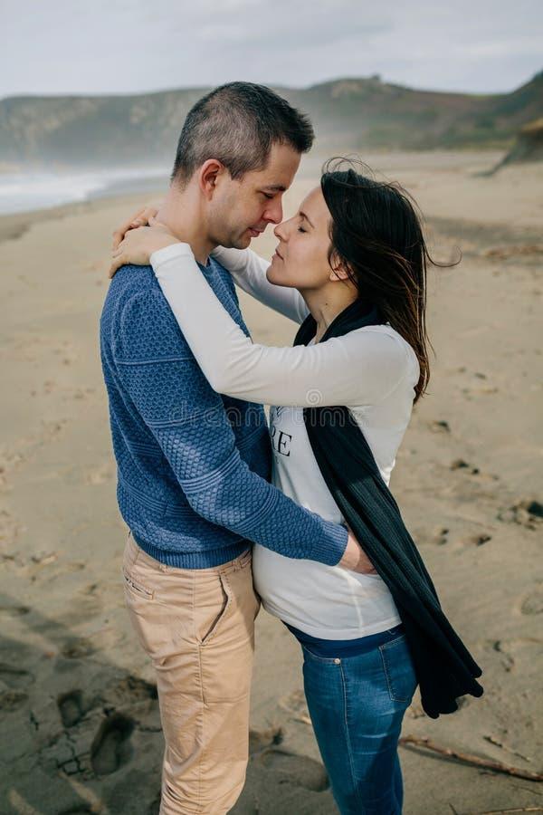 Femme enceinte étreignant l'associé sur la plage images libres de droits