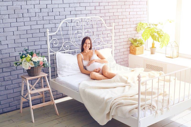 Femme enceinte affectueuse détendant dans la chambre à coucher photographie stock libre de droits