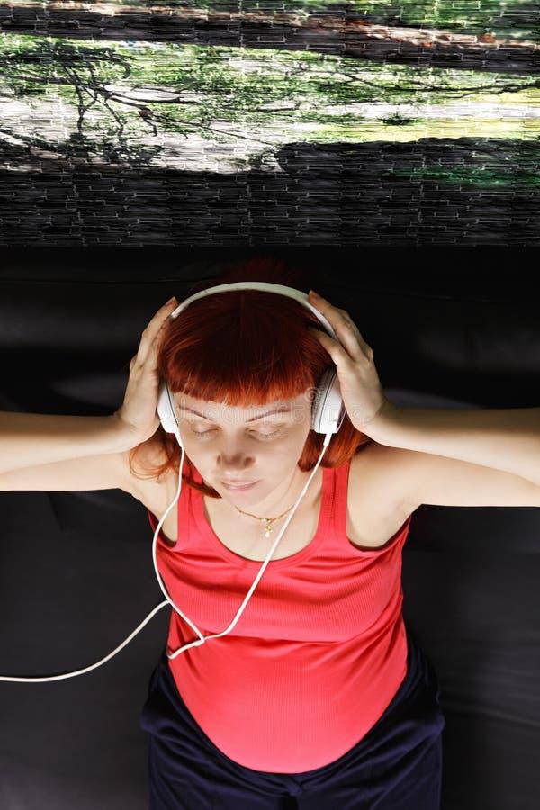 Femme enceinte appréciant des frais généraux de musique images libres de droits