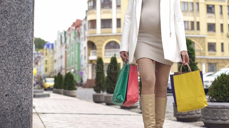 Femme enceinte appréciant son état marchant pour la promenade et faisant l'achat, en gros plan images libres de droits