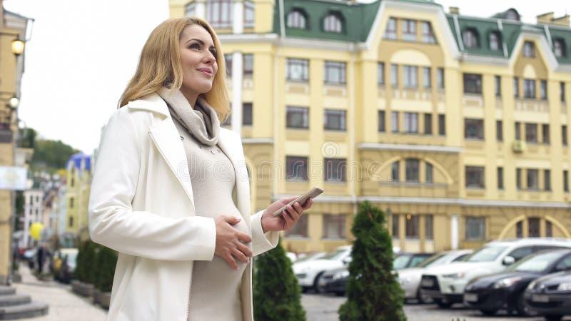 Femme enceinte attirante vérifiant le terme de l'accouchement dans rêver d'appli de smartphone photographie stock libre de droits