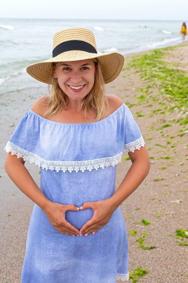 Femme enceinte au bord de la mer image stock