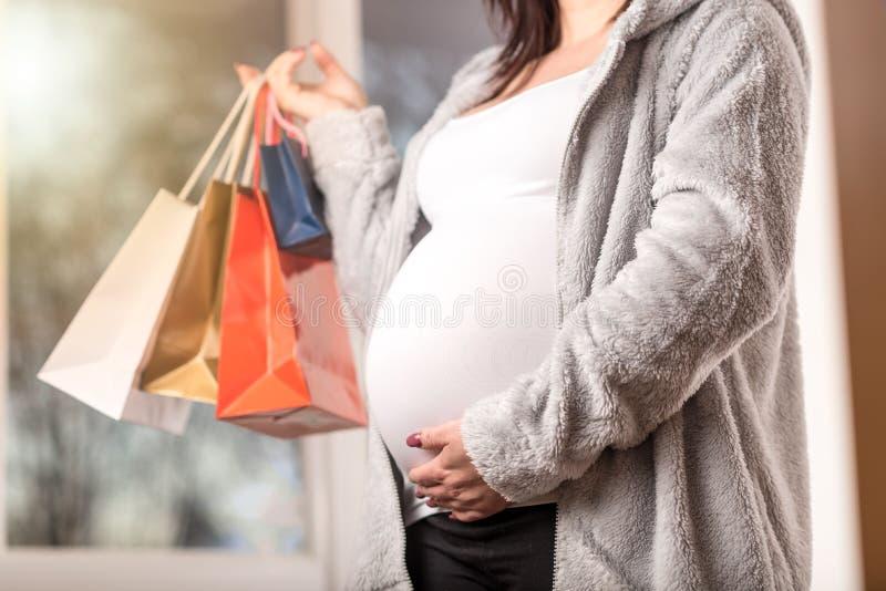 Femme enceinte avec des sacs à provisions touchant son ventre image libre de droits