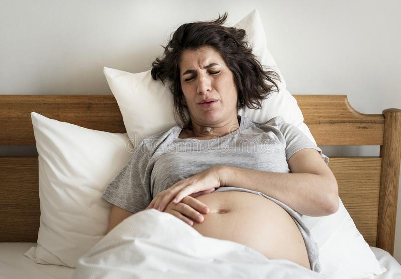 Femme enceinte avec douleur de travail image stock