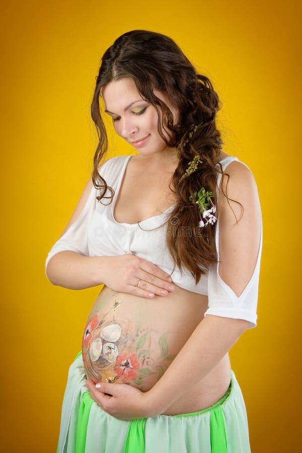 Femme enceinte avec la peinture d'arti de corps sur son ventre photos libres de droits
