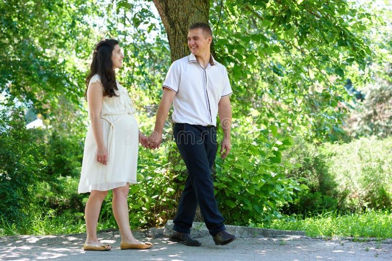 Femme enceinte avec le mari marchant pendant parc de ville, portrait de famille, la saison d'été, herbe verte et arbres photo libre de droits