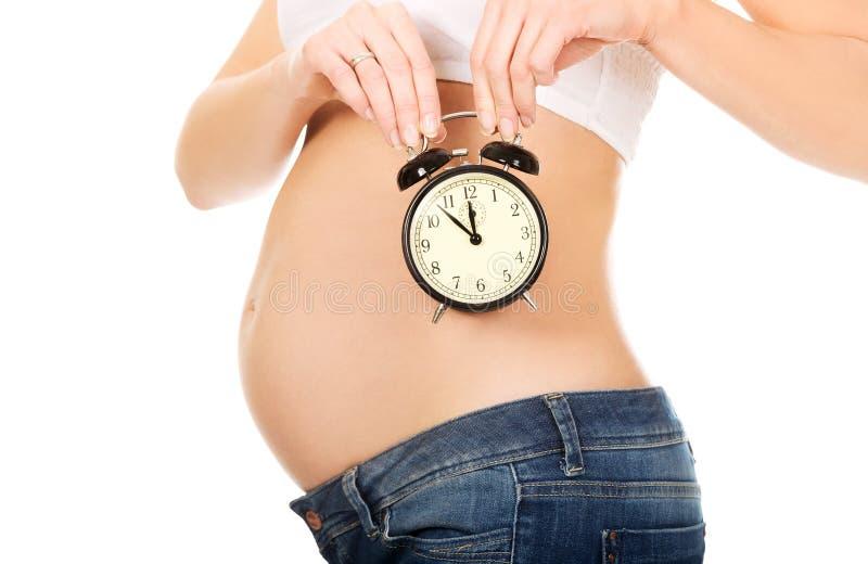 Femme enceinte avec une horloge d'alarme images libres de droits