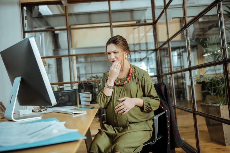 Femme enceinte ayant le mal de dents fort au travail image stock