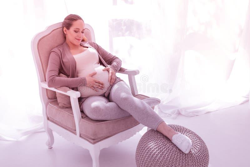 Femme enceinte belle blonde dans des vêtements confortables semblant heureux photographie stock