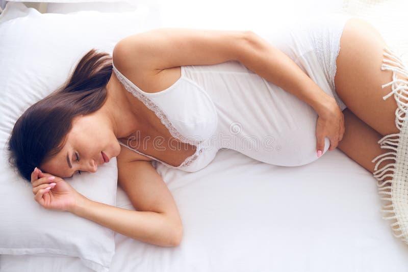 Femme enceinte décontractée dormant paisiblement sur le lit photos libres de droits
