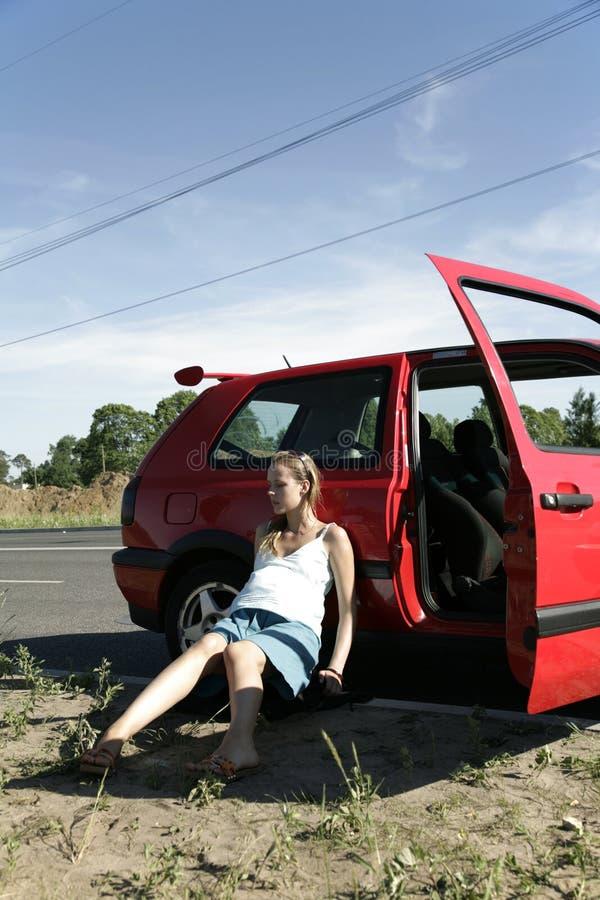 Femme enceinte délaissée s'asseyant près du véhicule rouge image libre de droits