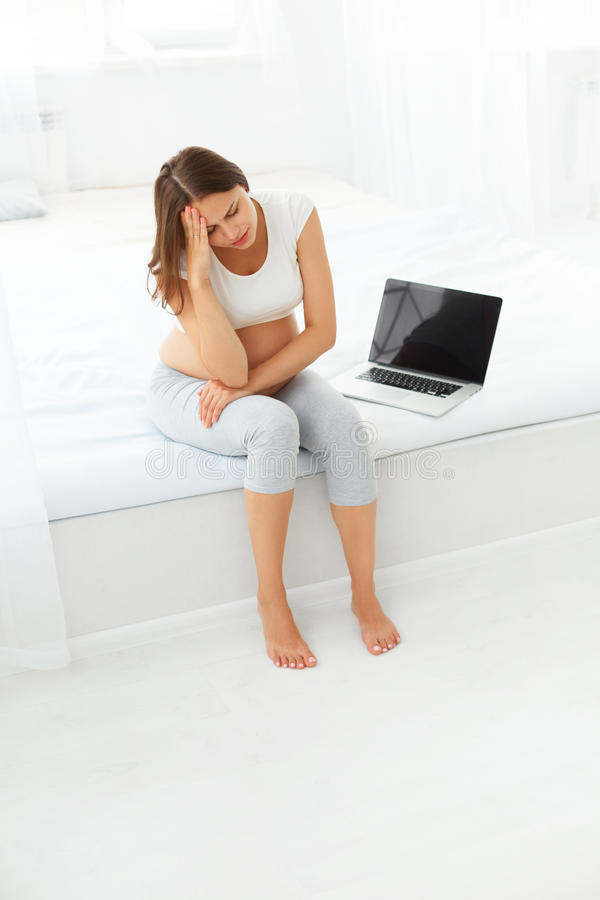 Femme enceinte déprimée avec un ordinateur portable tout en se reposant dessus photo stock