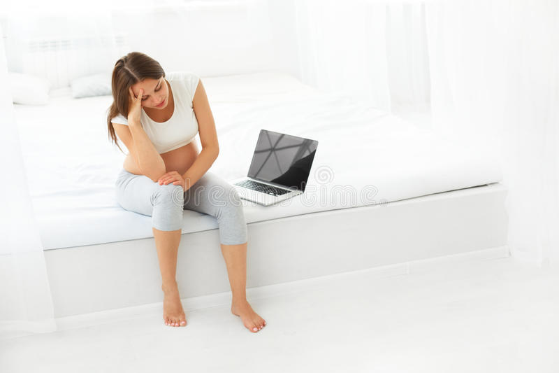 Femme enceinte déprimée avec un ordinateur portable tout en se reposant dessus image libre de droits