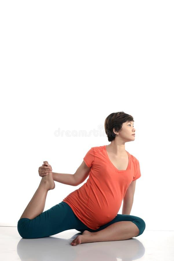 Femme enceinte d'Asiatique faisant le yoga photo libre de droits